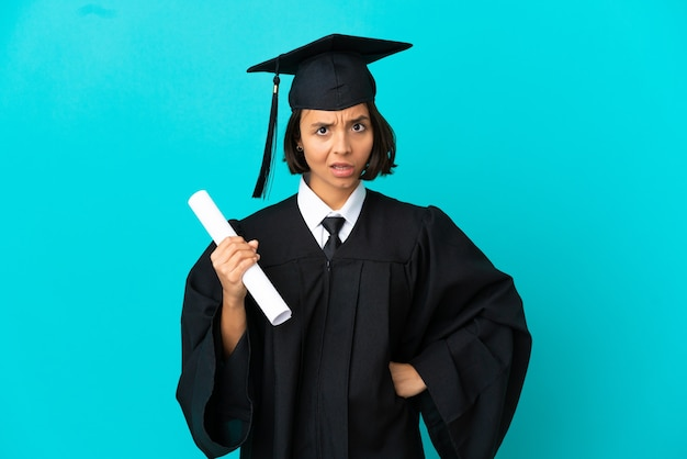 Jong universitair gediplomeerd meisje over geïsoleerde blauwe achtergrond boos