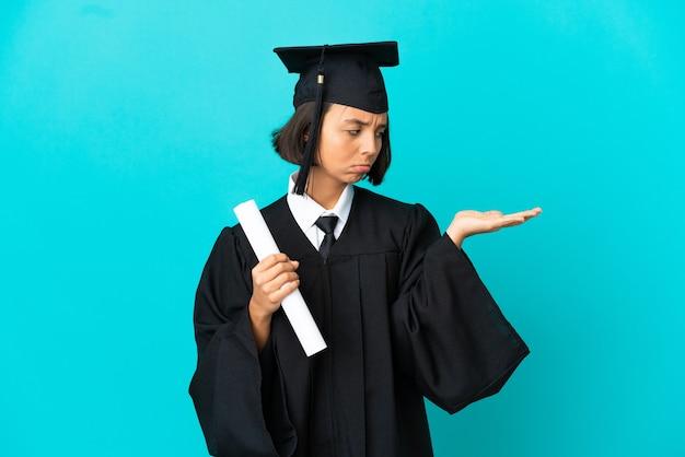 Jong universitair gediplomeerd meisje over geïsoleerde blauwe achtergrond die copyspace met twijfels houdt