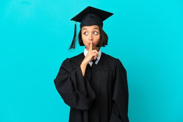 Jong universitair gediplomeerd meisje over geïsoleerde blauwe achtergrond die een teken van stiltegebaar toont dat vinger in mond stopt