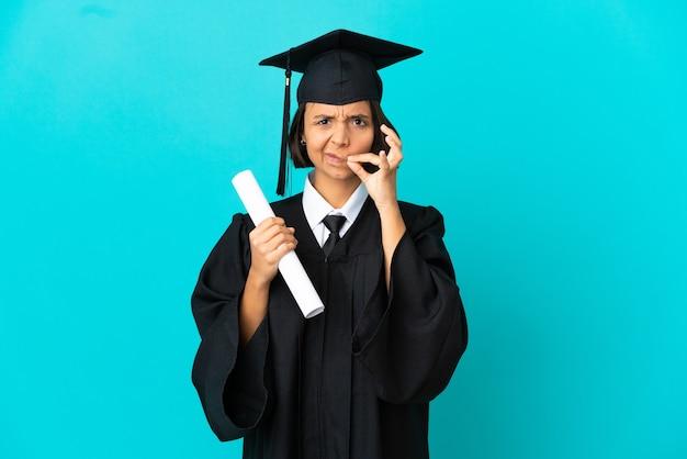 Jong universitair gediplomeerd meisje over geïsoleerde blauwe achtergrond die een teken van stiltegebaar toont