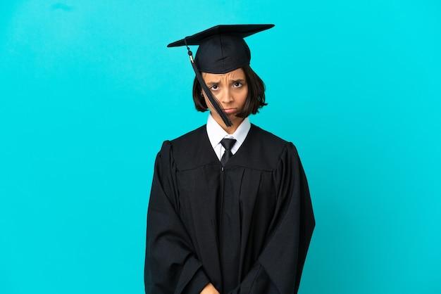 Jong universitair gediplomeerd meisje over geïsoleerde blauwe achtergrond met droevige uitdrukking