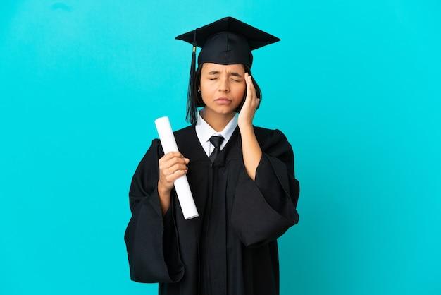 Jong universitair gediplomeerd meisje over geïsoleerde blauwe achtergrond met hoofdpijn