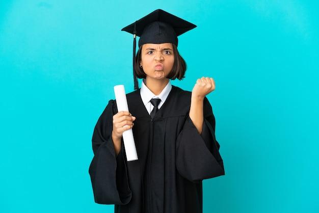 Jong universitair gediplomeerd meisje over geïsoleerde blauwe achtergrond met ongelukkige uitdrukking