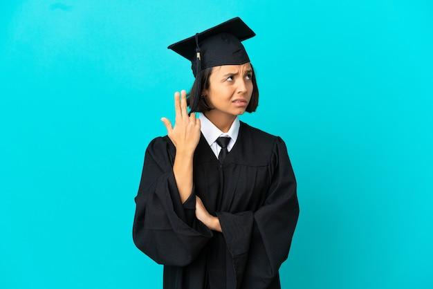 Jong universitair gediplomeerd meisje over geïsoleerde blauwe achtergrond met problemen die zelfmoordgebaar maken