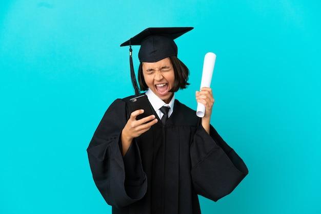 Jong universitair gediplomeerd meisje over geïsoleerde blauwe achtergrond met telefoon in overwinningspositie