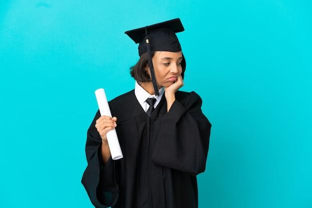Jong universitair gediplomeerd meisje over geïsoleerde blauwe achtergrond met vermoeide en verveelde expressie