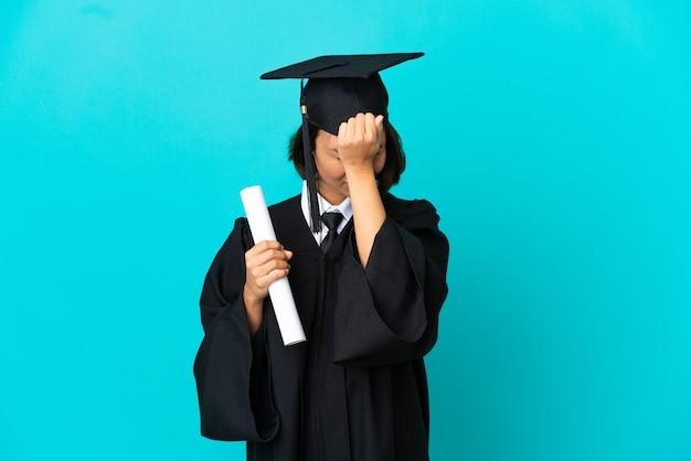 Jong universitair gediplomeerd meisje over geïsoleerde blauwe muur met hoofdpijn