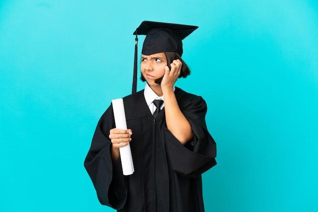 Jong universiteitsgediplomeerd meisje over geïsoleerde blauwe achtergrond die twijfels heeft terwijl het hoofd krabben