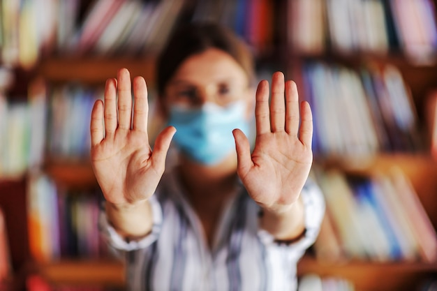 Jong universiteitsmeisje met gezichtsmasker bij status in bibliotheek en schone handen te tonen. covid pandemie concept.
