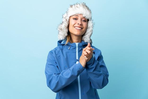 Jong uruguayaans meisje met de winterhoed dat bij het blauwe muur toejuichen wordt geïsoleerd