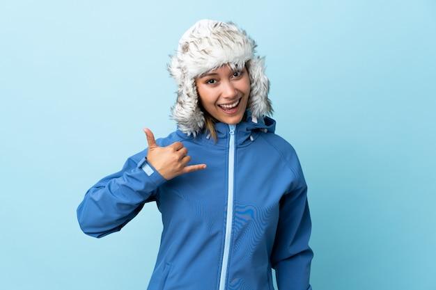 Jong uruguayaans meisje met de winterhoed dat op blauw wordt geïsoleerd dat telefoongebaar maakt