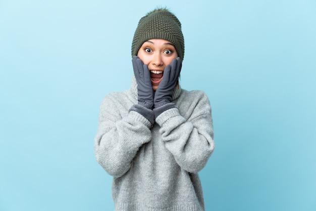 Jong uruguayaans meisje met de winterhoed dat op blauwe achtergrond met verrassingsgelaatsuitdrukking wordt geïsoleerd
