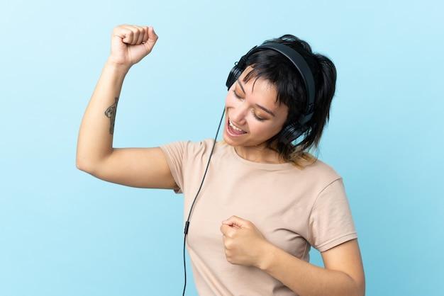 Jong uruguayaans meisje over blauwe muur luisteren muziek en dansen
