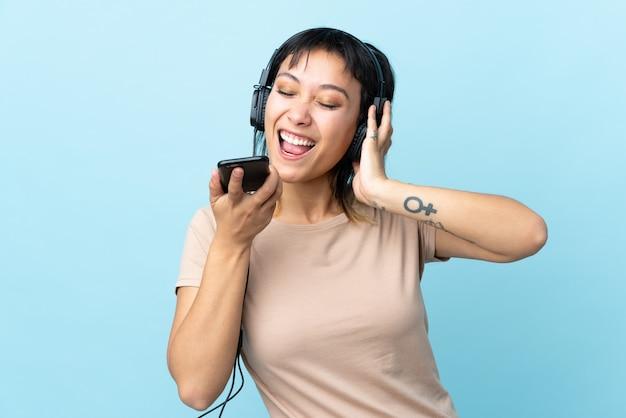 Jong uruguayaans meisje over blauwe muur luisteren muziek met een mobiel en zingen