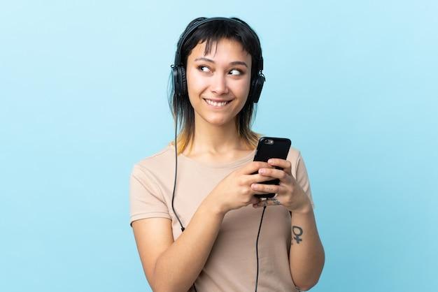 Jong uruguayaans meisje over geïsoleerde blauwe muur het luisteren muziek met mobiel en het denken