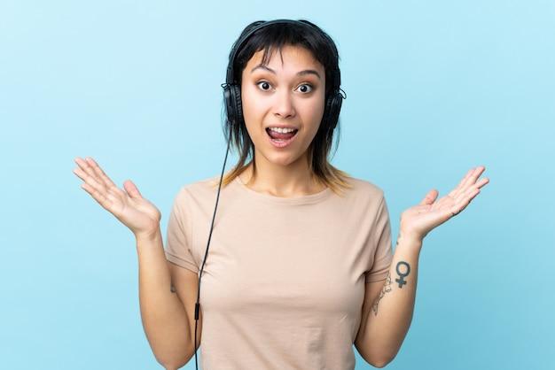 Jong uruguayaans meisje over geïsoleerde blauwe muur verrast en het luisteren muziek