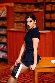 Jong verleidelijk studentenmeisje die in korte rok de boekzitting op de lijst lezen