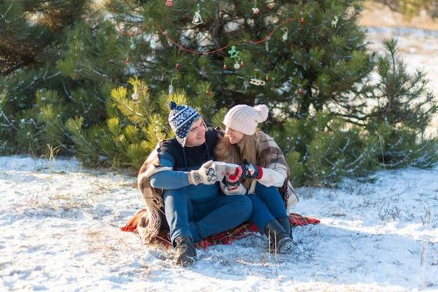 Jong verliefd paar drinkt een warme drank met marshmallows, zit in de winter in het bos, verstopt in warme, comfortabele tapijten en geniet van de natuur. ze praten en lachen om een kop warme dranken in het bos