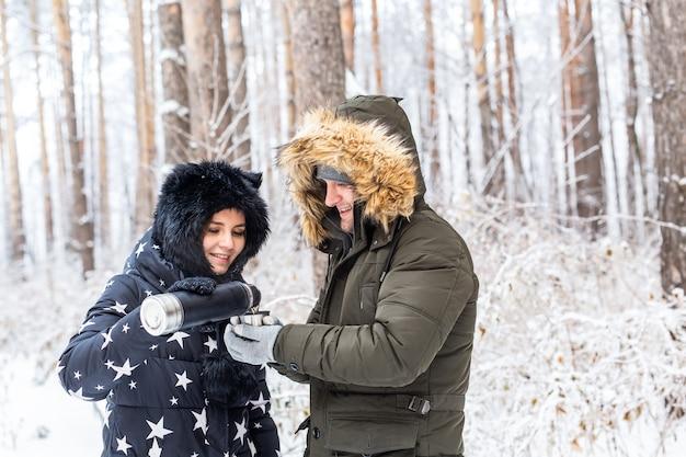 Jong verliefd stel drinkt een warm drankje uit een thermoskan en geniet van de winterse natuur.