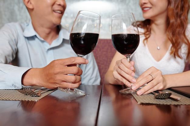 Jong verliefd stel drinkt rode wijn als aperitief tijdens het wachten op bestelling in restaurant