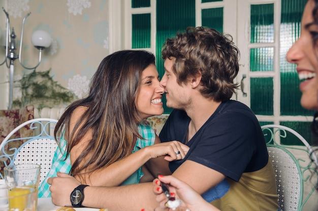 Jong verliefd stel lachen en omarmen thuis ontbijt met vrienden