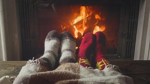 Jong verliefd stel liggend onder deken bij de open haard
