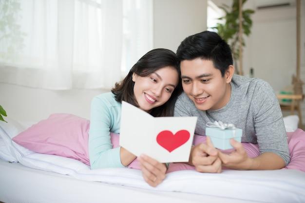 Jong verliefd stel maakt een cadeau aan elkaar op valentijnsdag.