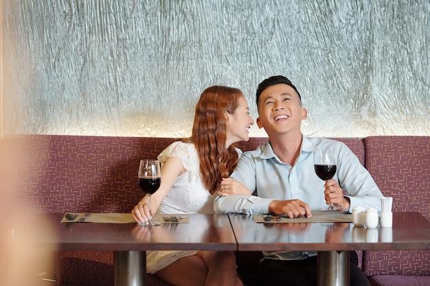 Jong verliefd stel maakt grapjes en lacht wanneer ze aan de tafel van het restaurant zitten, wijn drinken en wachten op eten
