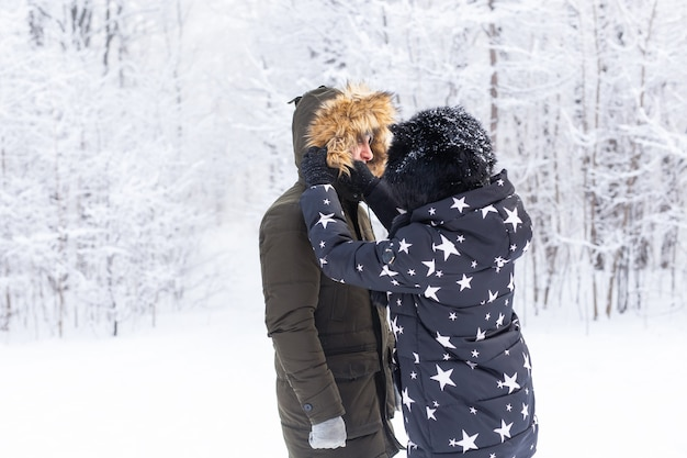 Jong verliefd stel veel plezier in het besneeuwde bos. actieve wintervakanties.