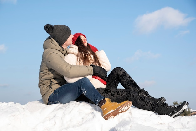 Jong verliefd stel zit op sneeuw tegen de blauwe lucht en lacht.