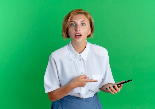 Jong verrast blond russisch meisje houdt en wijst op telefoon die camera bekijkt die op groene achtergrond met exemplaarruimte wordt geïsoleerd