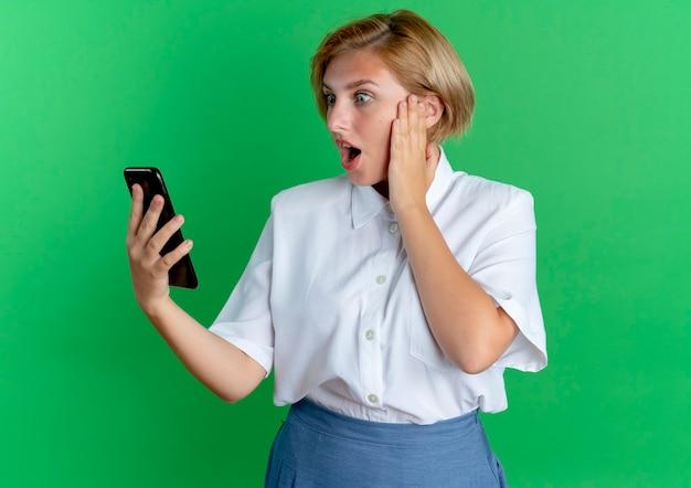Jong verrast blond russisch meisje legt hand op gezicht kijken naar telefoon geïsoleerd op groene achtergrond met kopie ruimte