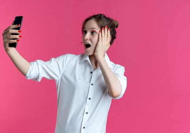 Jong verrast blond russisch meisje legt hand op gezicht kijken naar telefoon
