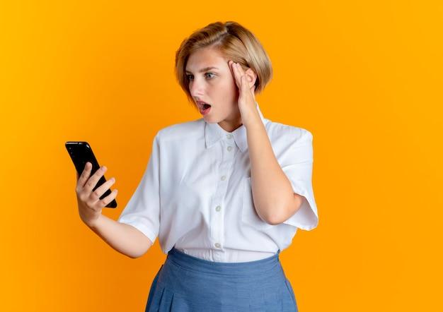 Jong verrast blond russisch meisje legt hand op hoofd houden en kijken naar telefoon geïsoleerd op een oranje achtergrond met kopie ruimte