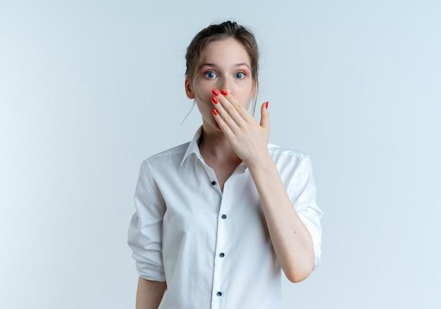 Jong verrast blond russisch meisje legt hand op mond geïsoleerd op een witte achtergrond met kopie ruimte