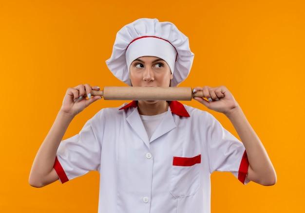 Jong verrast kaukasisch kokmeisje in eenvormige chef-kok houdt en beweert deegroller te bijten die op oranje achtergrond met exemplaarruimte wordt geïsoleerd