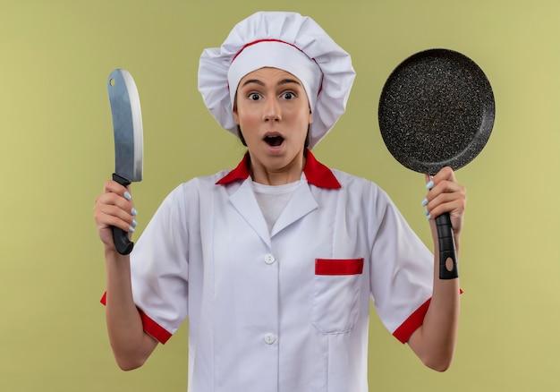 Jong verrast kaukasisch kokmeisje in eenvormige chef-kok houdt mes en koekenpan die op groene ruimte met exemplaarruimte wordt geïsoleerd