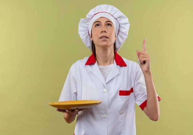 Jong verrast kaukasisch kokmeisje in eenvormige chef-kok houdt plaat en wijst omhoog geïsoleerd op groene achtergrond met exemplaarruimte