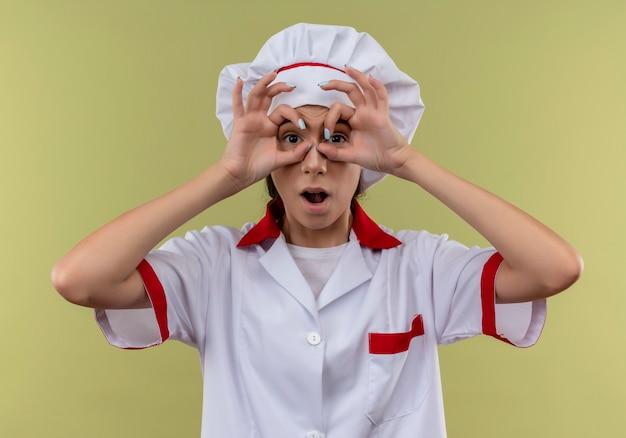 Jong verrast kaukasisch kokmeisje in eenvormige chef-kok kijkt door vingers die op groene achtergrond met exemplaarruimte worden geïsoleerd