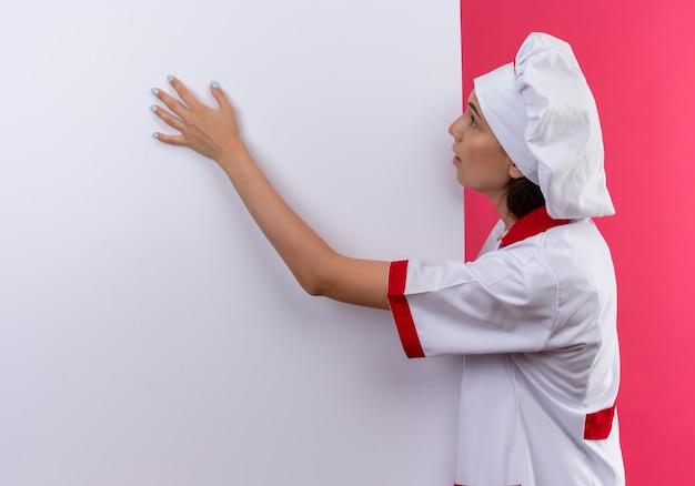 Jong verrast kaukasisch kokmeisje in eenvormige chef-kok ziet eruit en legt hand op witte muur op roze met exemplaarruimte