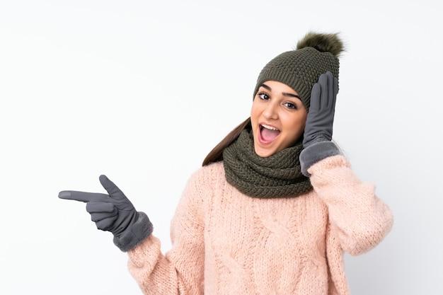 Jong verrast meisje met de winterhoed en wijzende vinger aan de kant