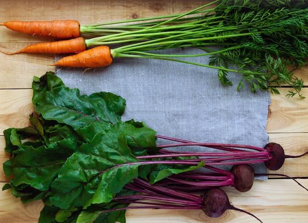 Jong vers geplukte bieten en wortelen op een hout. bovenaanzicht