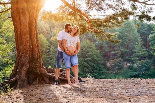 Jong verwacht paar hand in hand op buik onder de boom bij zonsondergang