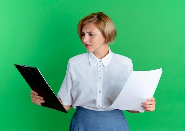 Jong verward blond russisch meisje houdt vellen papier en kijkt naar klembord geïsoleerd op groene achtergrond met kopie ruimte
