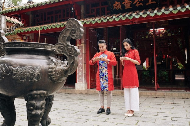 Jong vietnamees koppel in traditionele kostuums bidden met rokende stokken in handen in de boeddhistische tempel