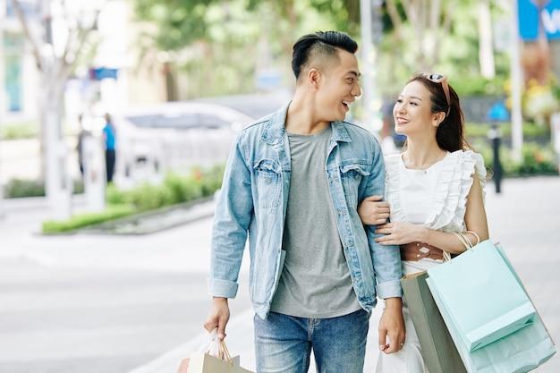 Jong vietnamees verliefd koppel kijken elkaar aan tijdens het wandelen op straat met papieren zakken na het winkelen