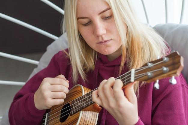 Jong volwassen blondemeisje die ukelele leren spelen, online gitaar leren, selectieve nadruk