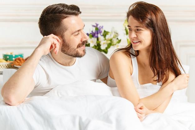 Jong volwassen heteroseksueel paar dat op bed in slaapkamer ligt Premium Foto