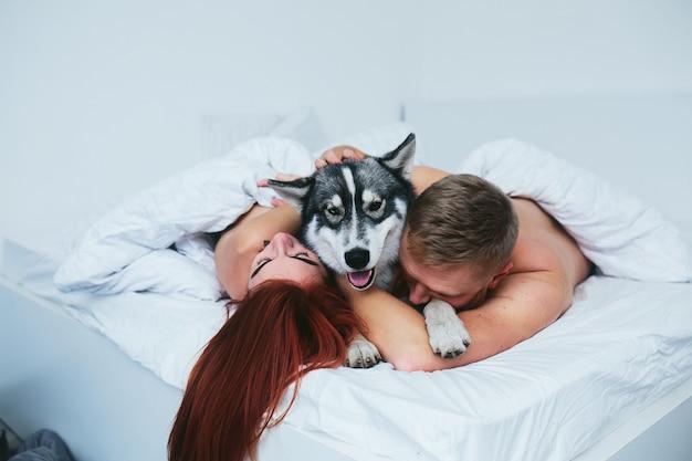 Jong volwassen heteroseksueel paar liggend op bed in de slaapkamer, samen met een hond