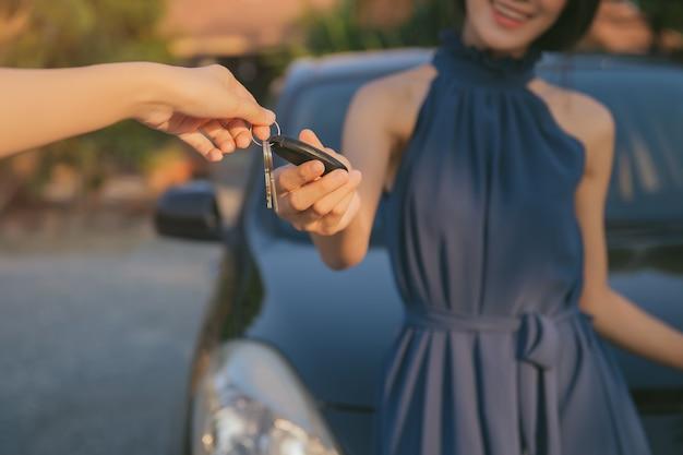 Jong volwassen meisje ontvangt de afstandsbediening door slimme sleutel van haar nieuwe auto